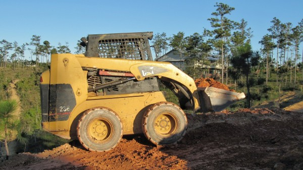 A skid steer at work moving dirt